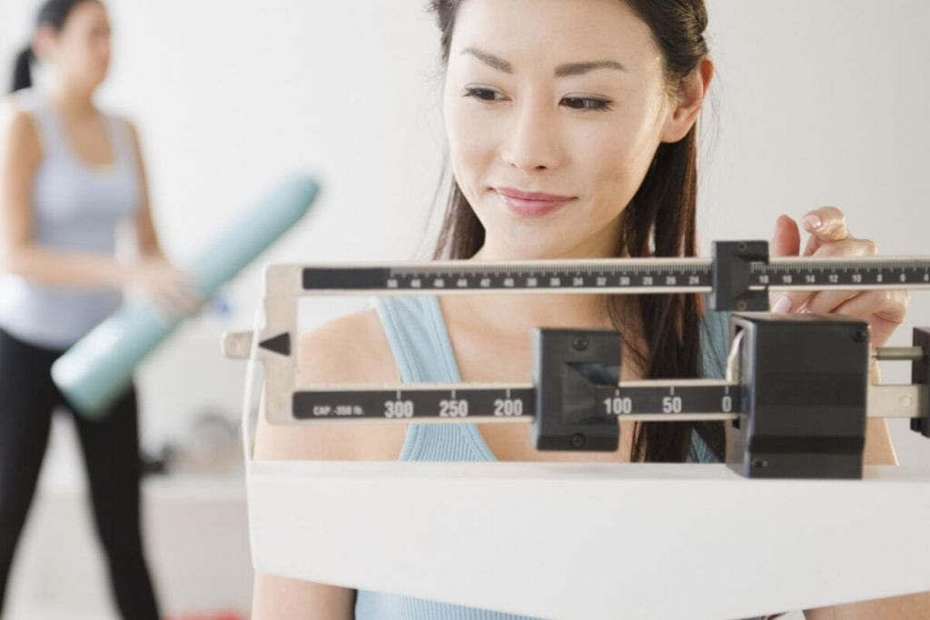 Asian woman weighs herself to lose weight with Kaenz.