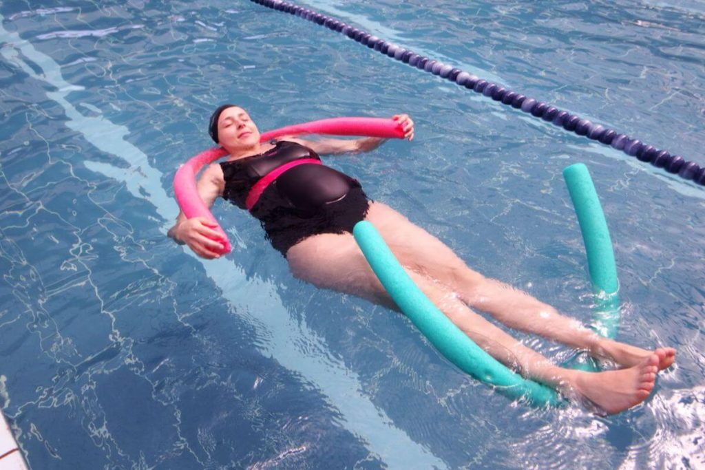Woman doing swimming for pregnant women in swimming pool.