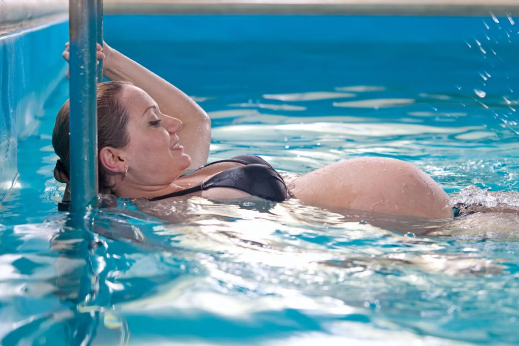Woman doing swimming for pregnant women in a heated pool.