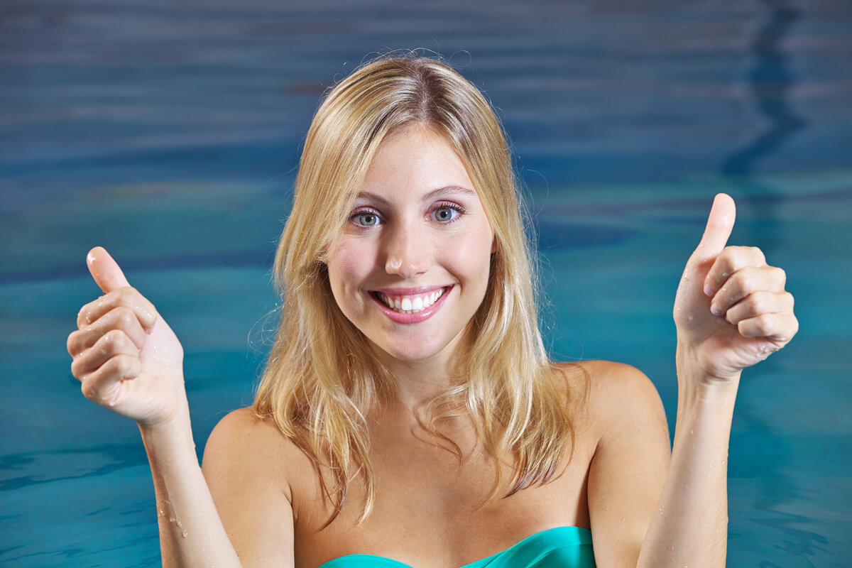Woman contented by treatment for fibromyalgia in swimming pool.