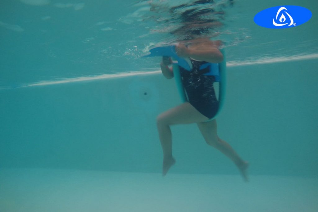 Woman with musculoskeletal conditions, doing Kaenz aquatic exercise in swimming pool.