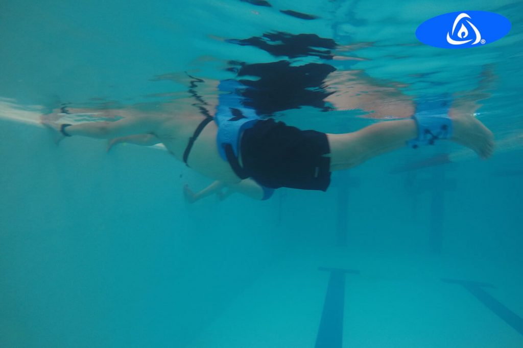 Swimmer swimming in water temperate and doing Kaenz aquatic exercise.